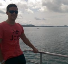 Alfred standing on a boat in the Qingdao sea
