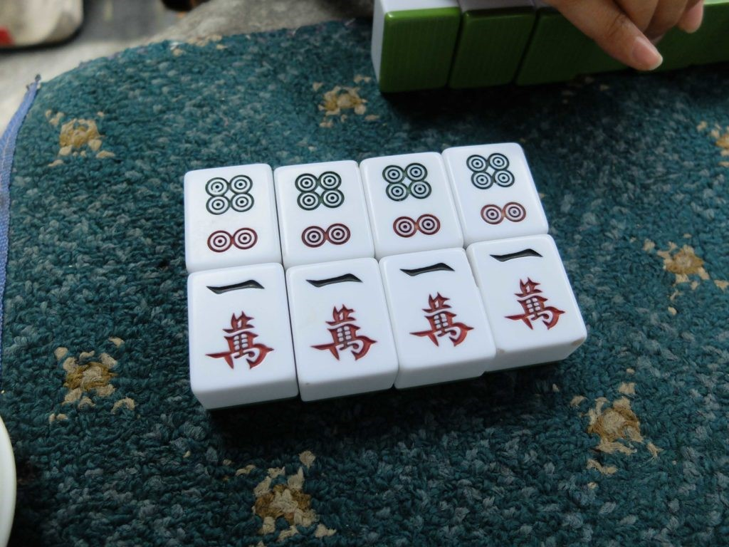 two kong mahjong tiles on green table