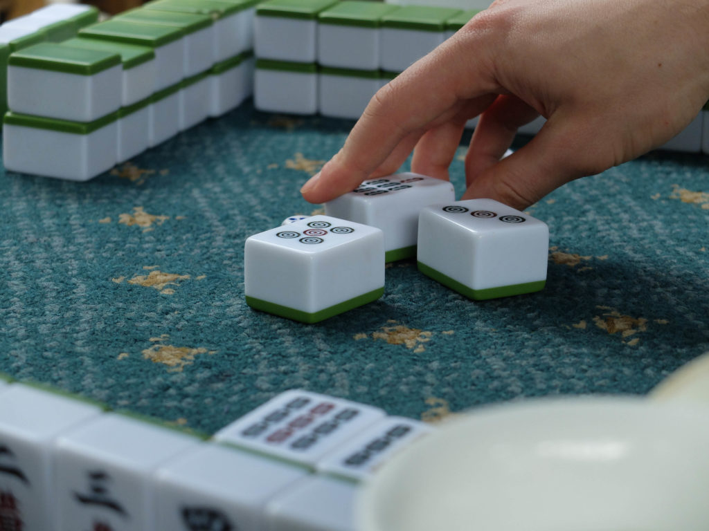 hand picking up mahjong tile from table