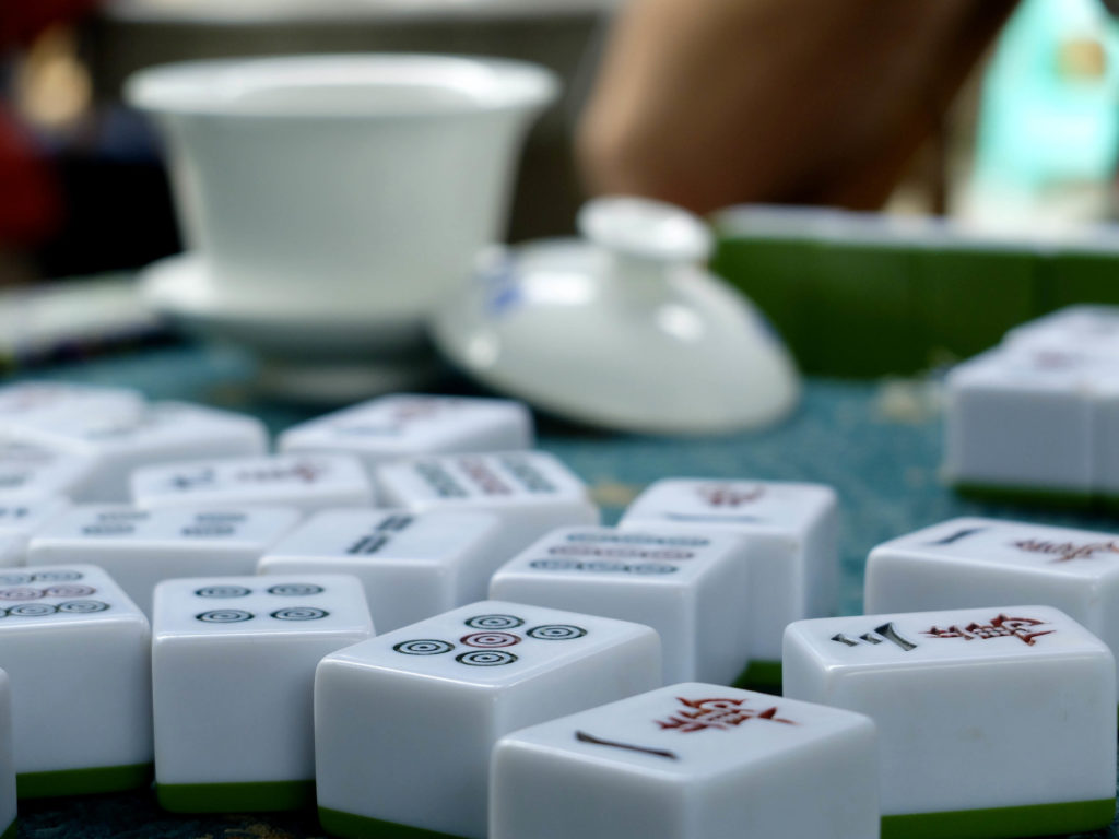 mahjong tiles on a table in front of a teacup